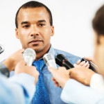 Male executive being questioned by journalists.